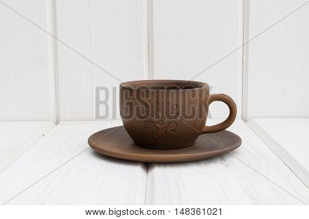 clay cup and saucer clay cup and saucer on a white wooden background
