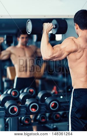 Body Building Champion Exercising In The Gym