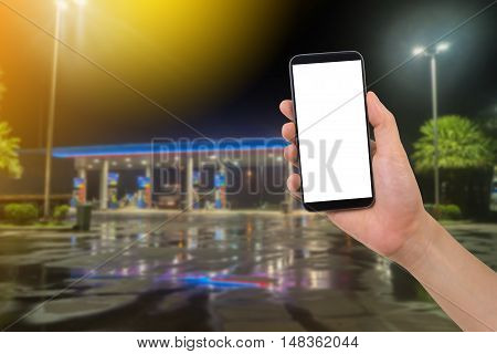 human hand hold smartphone tablet cell phone with blank screen on blurry filling station background finding service station concept.