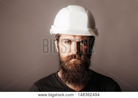 handsome bearded man worker with beard and mustache on serious face in building helmet or hard hat of builder or professional engineer on grey background