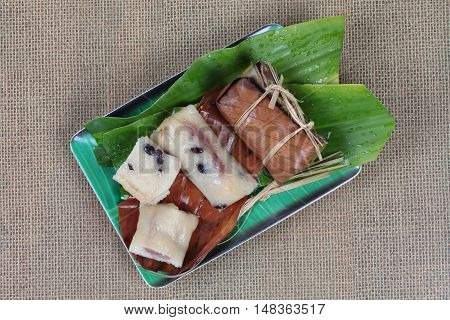 Streamed sticky rice and black bean  in banana leaf as