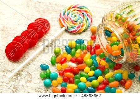 Glass bowl fallen with colorful jelly beans and a lollipop