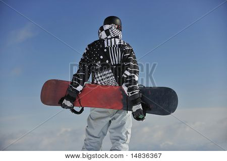 snowboarder relaxing and posing at sunny day on winter season with blue sky in background