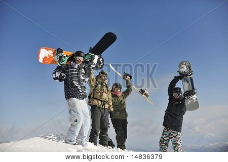 young snowboarders group have fun and relax at sunny winter day on winter season