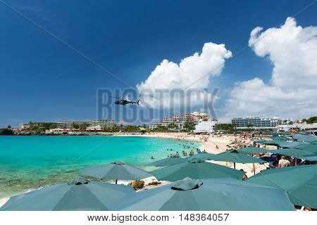 helicopter flies over the beach Maho bay Caribbean