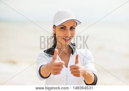 Young woman on beach listening to music in earphones from smart phone mp3 player smartphone armband, Female training for marathon on beautiful beach. Mixed race Asian woman.