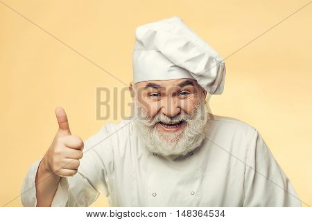 Bearded man cook with smiling face in chef hat with thumb up in studio on yellow background