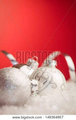 Extreme close up view of christmas baubles against red background
