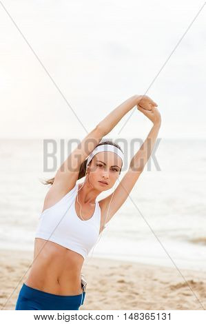 Young woman on beach listening to music in earphones from smart phone mp3 player, smartphone. Female training for marathon on beautiful beach. Mixed race Asian woman.