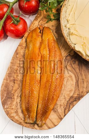 smoked herring filet slice of bread with butter tomatoes and parsley on a wooden board