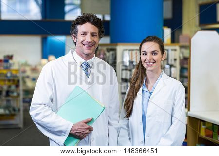 Portrait of smiling pharmacists standing with file in pharmacy