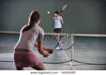 young girls playing tennis game indoori in tennis court