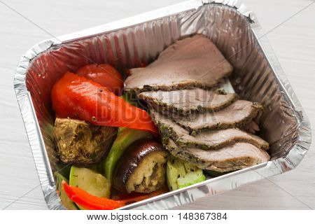 Healthy food delivery or take away, diet concept. Organic nutrition with protein, carb and fat balance. Weight loss dish in foil box. Baked vegetables and steamed veal.