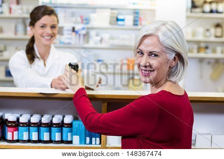 Portrait of pharmacist giving medicine to customer in pharmacy