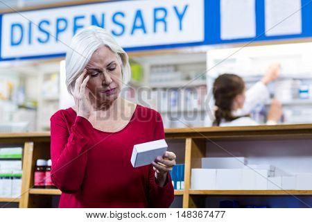 Tensed customer checking a pill box in pharmacy
