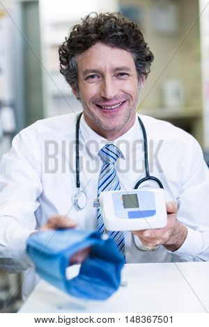 Portrait of pharmacist holding blood pressure monitor in pharmacy