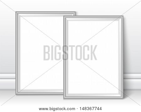 Frames near wall on the floor. Realistic vector silver photo frames ready for your design. Vector template for presentation your photo art posters paintings or other crafts.