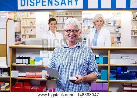 Portrait of customer holding prescription while checking medicine in pharmacy