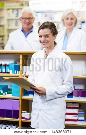 Portrait of pharmacist writing on file in pharmacy