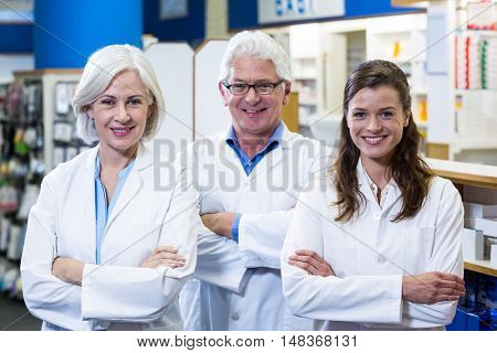 Portrait of smiling pharmacists standing with arms crossed in pharmacy