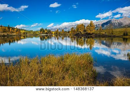 Canmore, near Banff. Concept hiking. Blue sky and clouds reflected in smooth water of the lake. Shining day in the Canadian Rockies