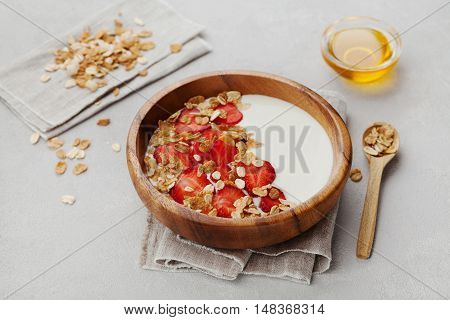 Homemade yogurt in wooden bowl with strawberry and granola or muesli on light table, healthy breakfast.