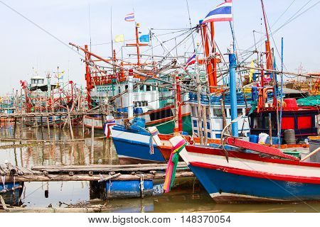Fishing boats off work and dock in a harbour .