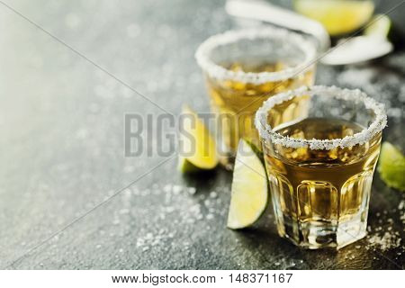 Tequila shot with lime and sea salt on black table, selective focus. Copy space for text. Vintage style.