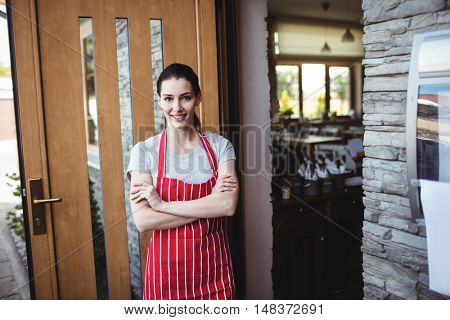 Portrait of female baker standing with arms crossed at the entrance of bakery shop