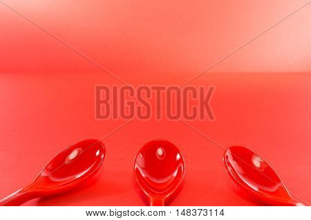 Three Red Plastic Spoons On Red Background