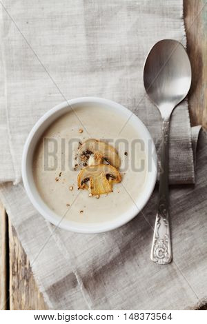 Cream soup with mushrooms champignon and potato in white bowl, vintage style. Top view.
