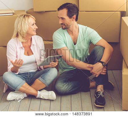 Beautiful mature couple in casual clothes is sitting on the floor among boxes talking and smiling while moving to the new apartment. Woman is using a tablet