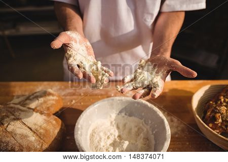 Mid-section of baker mixing flour by hand at bakery shop