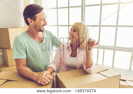 Beautiful mature couple in casual clothes is leaning on the boxes looking at each other and smiling while moving to the new apartment. Woman is holding keys