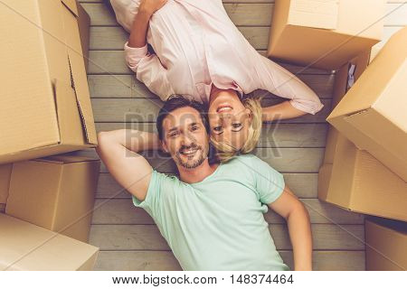 Top view of beautiful mature couple in casual clothes looking at camera and smiling while lying on the floor among boxes for move
