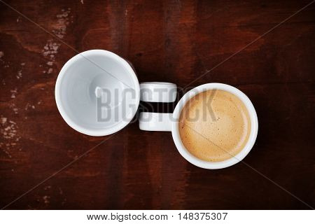 Empty and full cup of fresh coffee on rustic wooden table. Benefits and harms of coffee concept, top view.