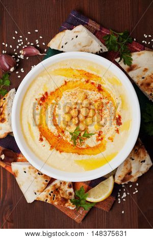 Hummus or houmous appetizer made of mashed chickpeas with tahini, lemon, garlic, olive oil, parsley and paprika. Top view. Flat lay.