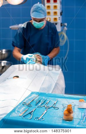 Close-up of surgical tool on tray and surgeon placing an oxygen mask on the face of a patient in background