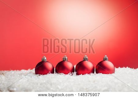 Composite image of Christmas baubles lined up against red background