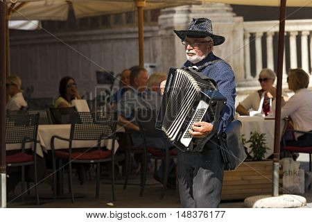 VERONA ITALY - SEPTEMBER 17 2016: Unidentified senior street musician plays the accordion in Dante Square for tourists sitting outside of restaurants