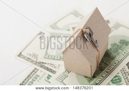 Model of cardboard house with key and dollar bills. Building , loan, real estate, cost of housing or buying a new home concept.