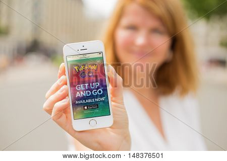 RIGA LATVIA - July 14 2016: Woman showing Pokemon Go website on the phone. Pokemon Go is a location-based augmented reality mobile game.