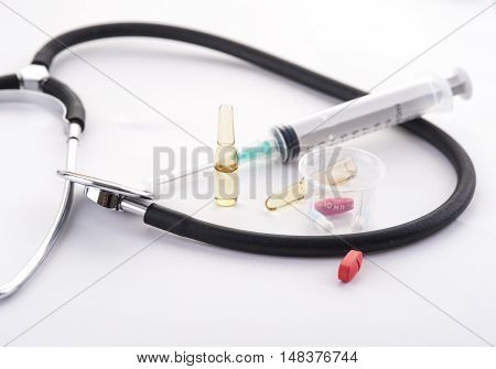 Stethoscope, syringe for injection, ampules and pills on white background. Selective focus. colorful medical equipment.