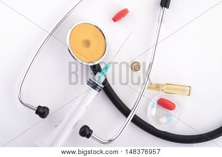 Red pills, ampules, syringe and stethoscope on white background. Top view. Colorful medical equipment.