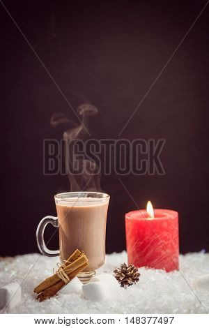 close up view of composite image of hot chocolate and candle against black background