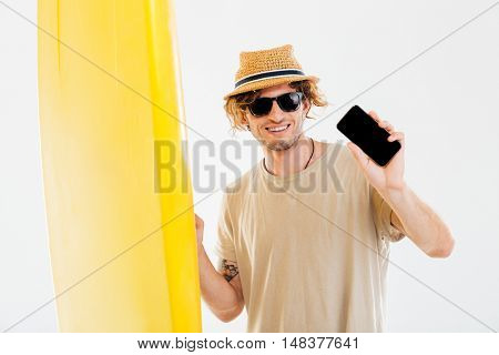 Portrait of a curly beach man in sunglasses and hat holding surfboard and showing blank screen smartphone isolated on the white background