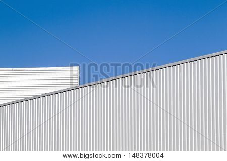 Corrugated sheet metal wall and roof against blue sky. Modern warehouse or storage. Outdoor. Industrial look. Digital background