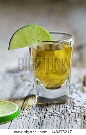 Tequila shot with lime and sea salt on rustic wooden board, selective focus. Vintage style.