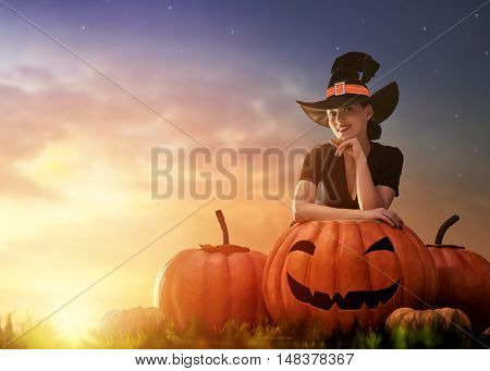 Happy Halloween! Beautiful young witch with a big pumpkin. Attractive woman in witch costume outdoors.