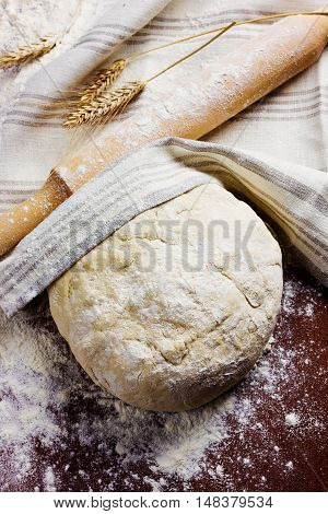 Homemade pizza or bread dough with rolling pin on the wooden table. Rustic style. Bakery concept.
